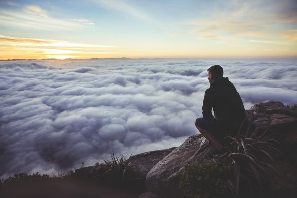 man-sitting-and-watching-clouds-from-mountain-top-1